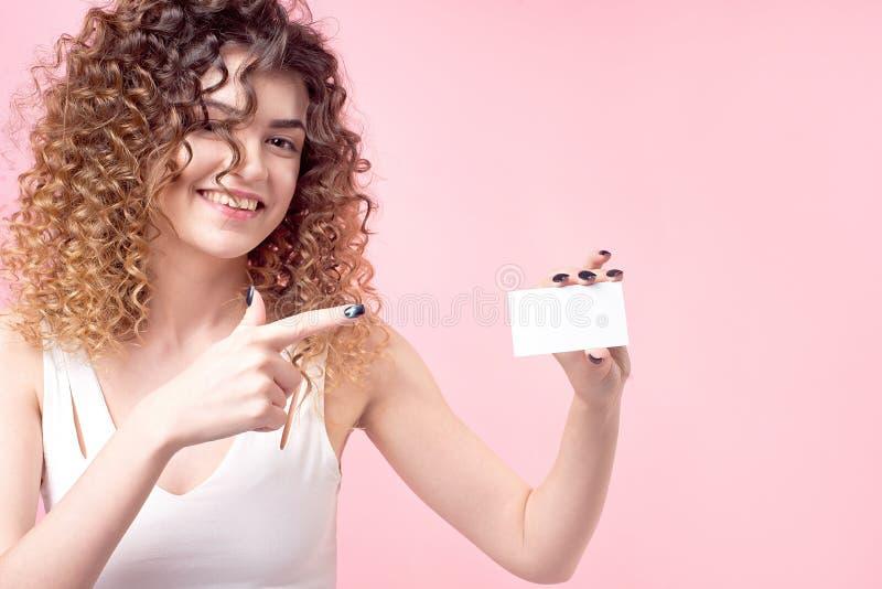 Młoda piękna dziewczyna z kędzierzawym włosy trzyma kartę w jej ręce i pokazuje je zdjęcia stock