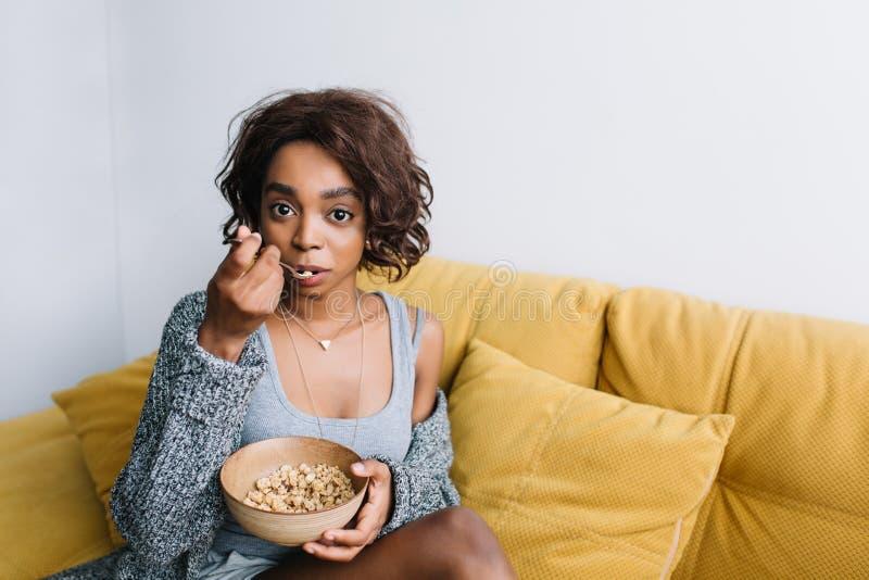 Młoda piękna dziewczyna z krótkim kędzierzawym włosy ma zdrowego śniadanie, je granola, muesli na żółtej leżance, kanapa dom obraz royalty free