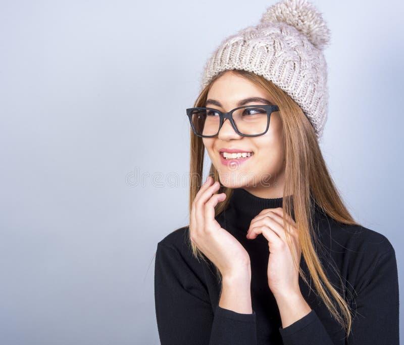 Młoda piękna dziewczyna z szkłami i zimy kapeluszowa pozycja przed popielatym tłem, mnóstwo czysta przestrzeń zdjęcia stock