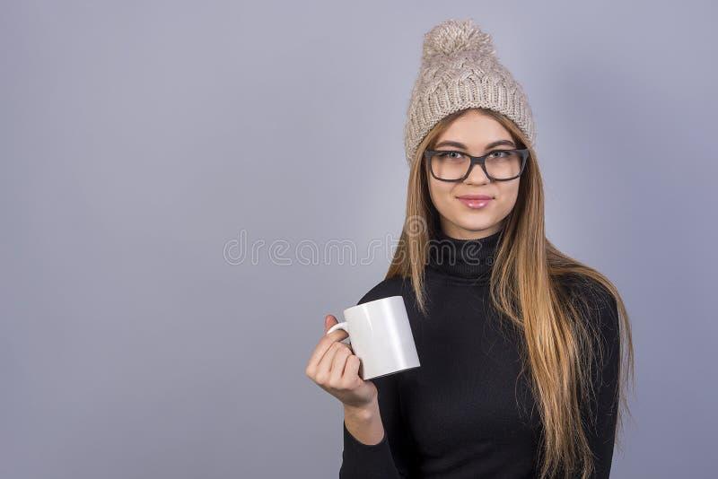 Młoda piękna dziewczyna z szkłami i zimy kapeluszowa pozycja tła, mienia i herbata lub kawa przed popielatą filiżanką obrazy royalty free
