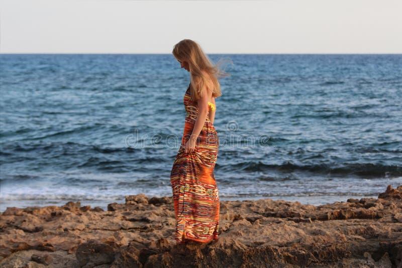 Młoda piękna dziewczyny pozycja z ukosa i mienie jej suknia zdjęcia royalty free
