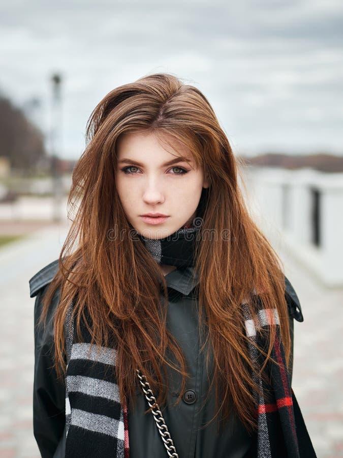 Młoda piękna emocjonalna rudzielec kobieta w eleganckim okopu żakiecie, duży szkocka krata szalik cieszy się wakacje czas wolnego fotografia stock