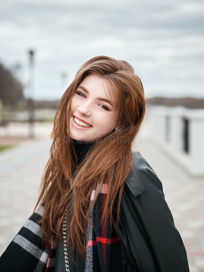 Młoda piękna emocjonalna rudzielec kobieta w eleganckim okopu żakiecie, duży szkocka krata szalik cieszy się wakacje czas wolnego obraz royalty free