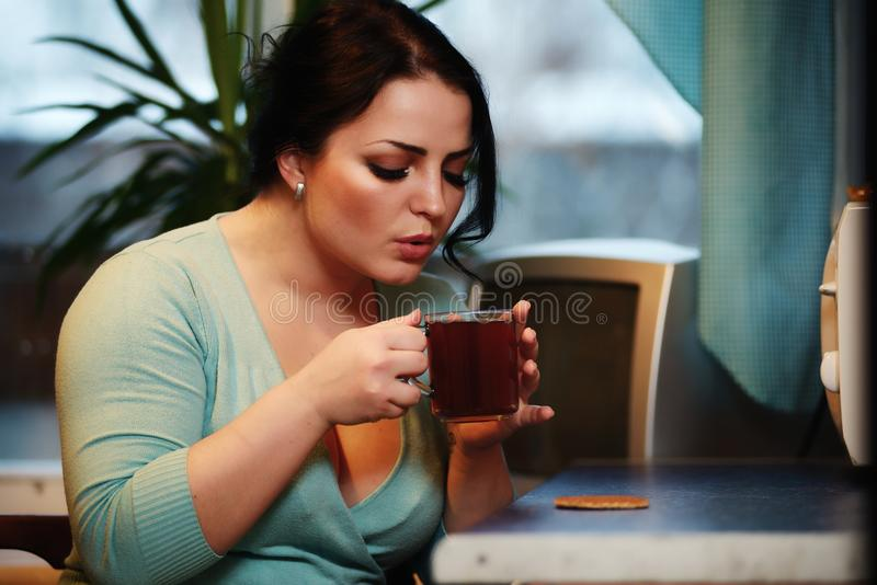 Młoda piękna gospodyni domowa pije herbaty w kuchni zdjęcie stock