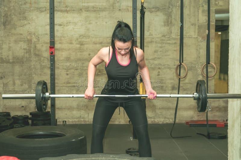 Młoda piękna i atrakcyjna dziewczyna tylnych mięśni dżdżownica w górę treningu z lekkim barbell ciężarem w gym, istni ludzie tren zdjęcie royalty free