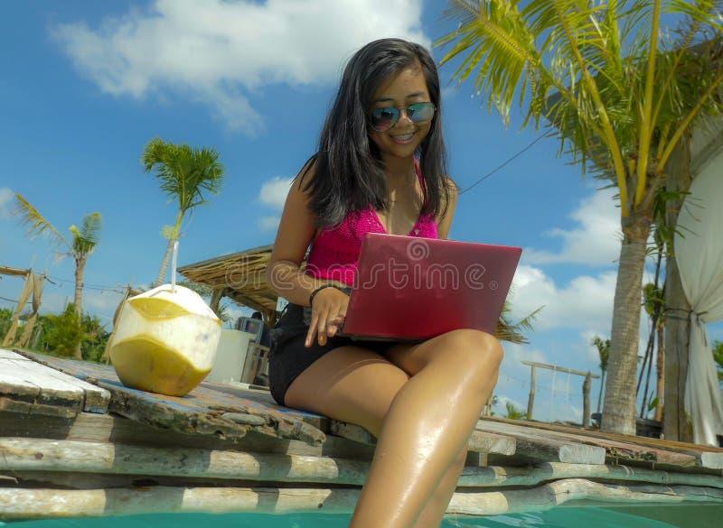 Młoda piękna i szczęśliwa Azjatycka Indonezyjska nastolatek kobieta w bikini przy tropikalnym kurortu basenu networking relaksują zdjęcia stock