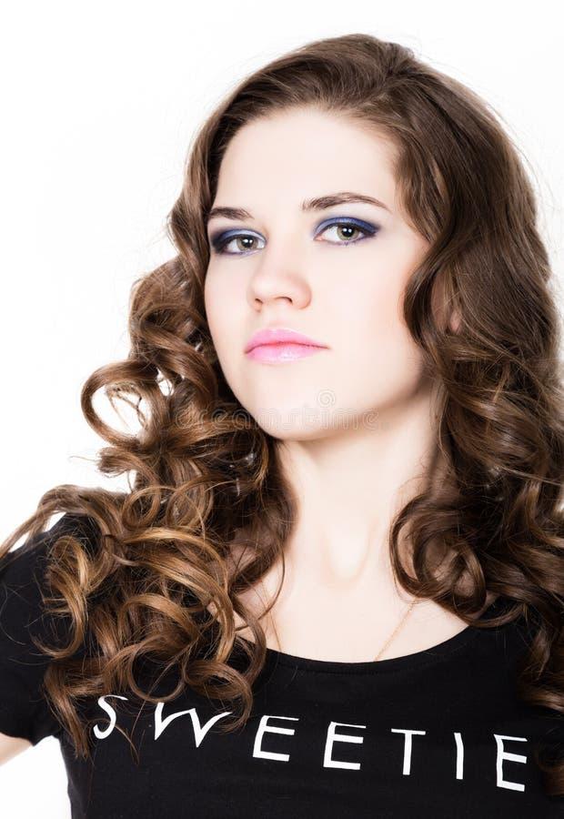 Młoda piękna kędzierzawa dziewczyna z fachowym makijażem zdjęcia stock