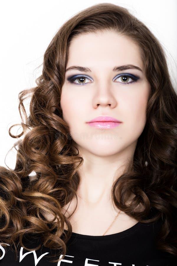 Młoda piękna kędzierzawa dziewczyna z fachowym makijażem zdjęcie royalty free