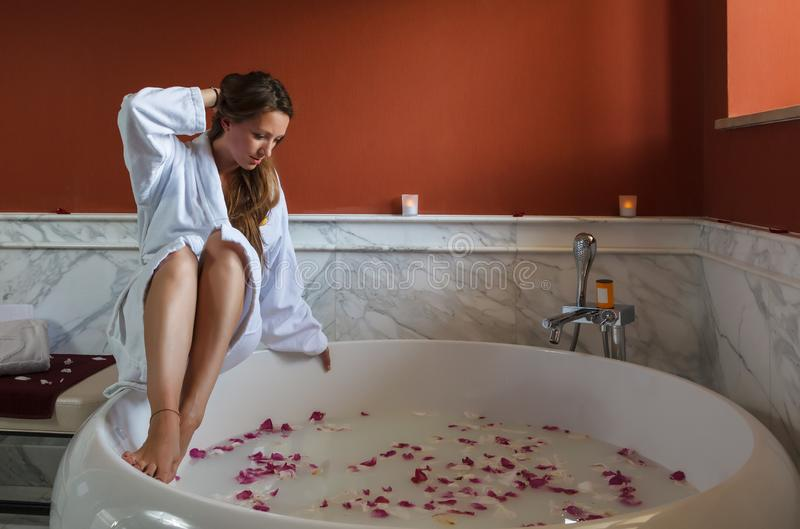 Młoda piękna Kaukaska brunetki kobieta w białym bathrobe jest wokoło mieć zdroju skąpanie z różanymi płatkami Wellness i odtwarza zdjęcie stock
