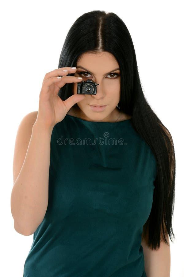 Młoda Piękna Kaukaska kobieta z małą zabawkarską kamerą nad białym tłem obrazy stock