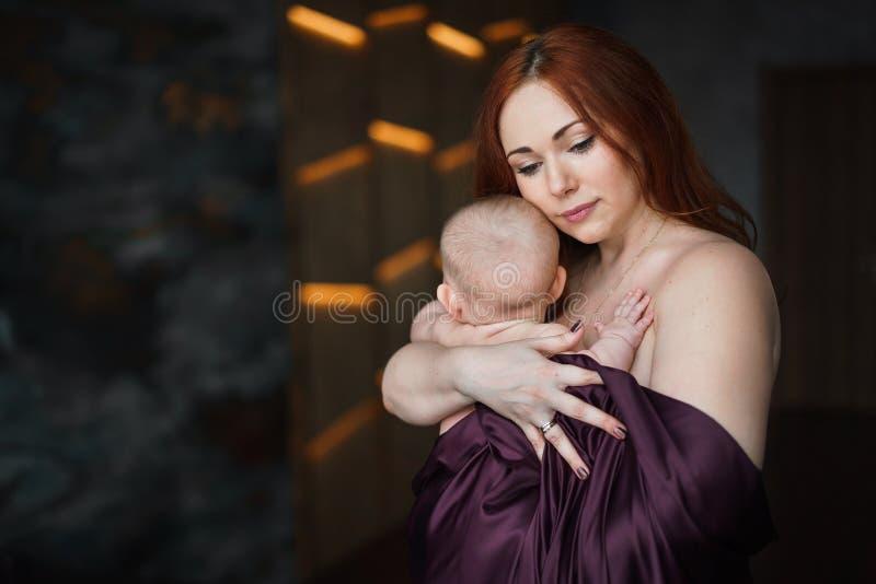 Młoda piękna kobieta ściska jej nowonarodzonego dziecka obraz royalty free