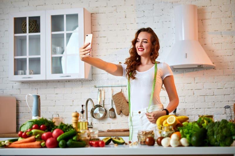 Młoda piękna kobieta bierze selfie podczas gdy gotujący w nowożytnej kuchni Zdrowy jedzenie i Dieting poj?cie strata wagi obrazy royalty free