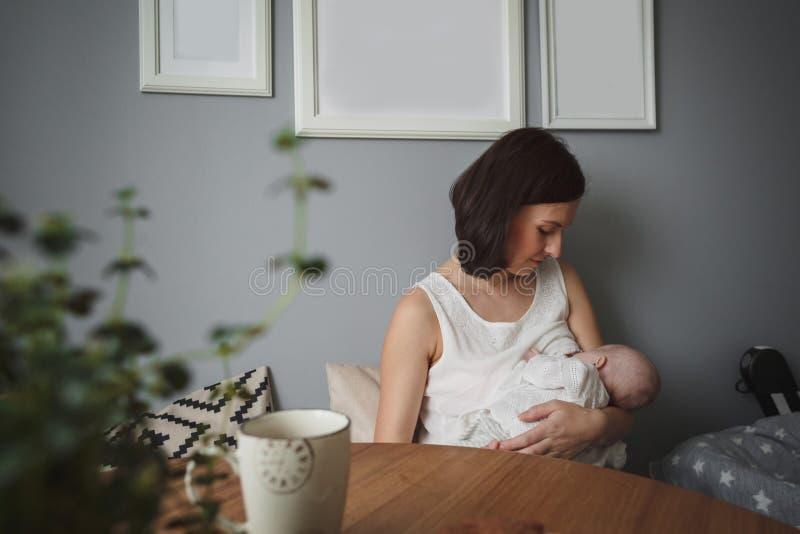 Młoda piękna kobieta breastfeeding troszkę dziecka w wygodnym pokoju zdjęcia royalty free