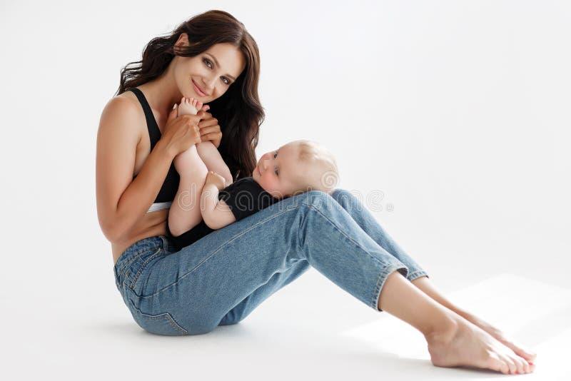 Młoda piękna kobieta, brunetka z długie włosy, pozuje w studiu z jej małym synem fotografia stock
