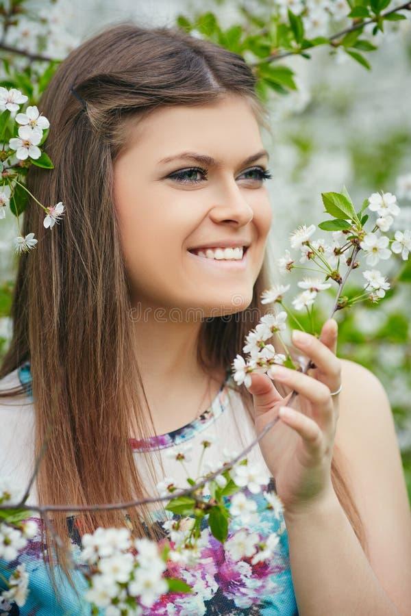 Młoda piękna kobieta cieszy się odór kwitnący drzewo na słonecznym dniu zdjęcia royalty free