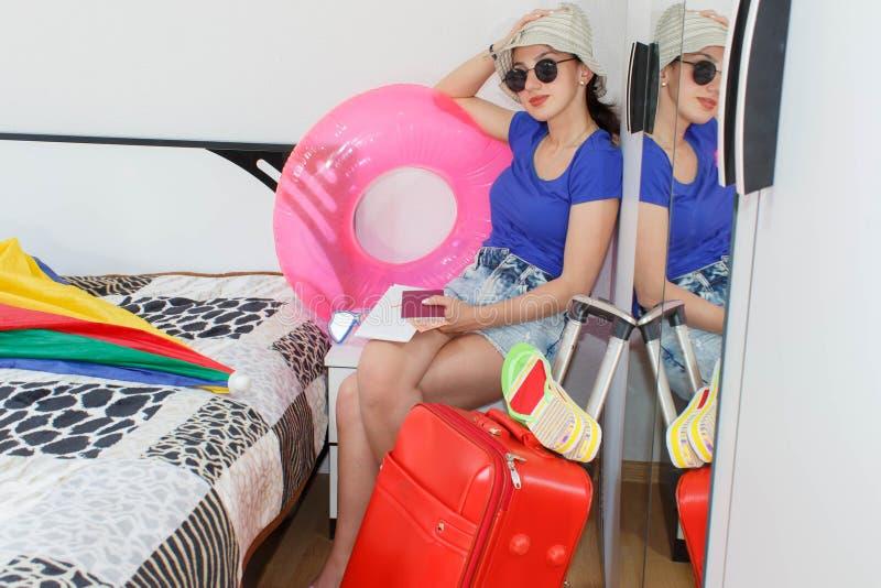 Młoda piękna kobieta, czerwona walizka, obsiadanie, czekanie, wakacje podróżuje wokoło światu, kolorowy, obraz royalty free