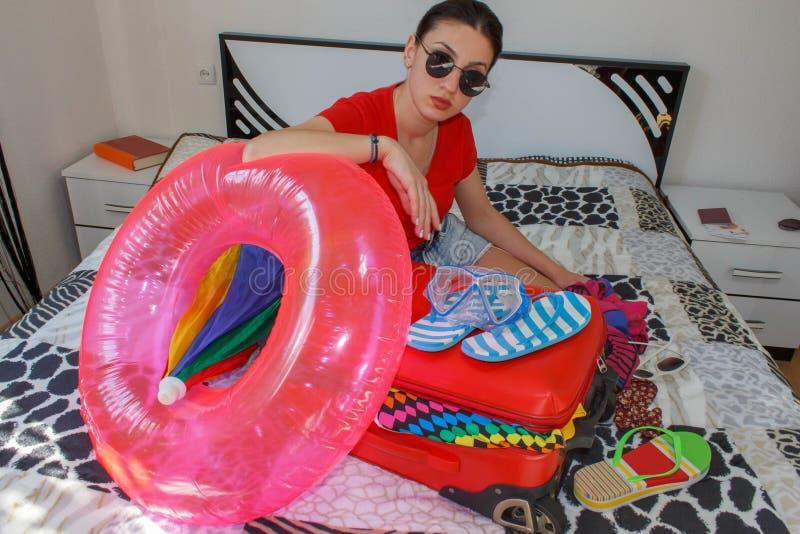 Młoda piękna kobieta, czerwona walizka, obsiadanie, czekanie, wakacje podróżuje wokoło światu, kolorowy, obrazy stock