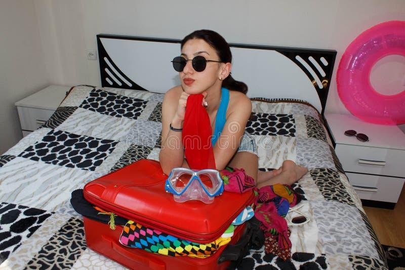 Młoda piękna kobieta, czerwona walizka, obsiadanie, czekanie, wakacje podróżuje wokoło światu, kolorowy, zdjęcia stock