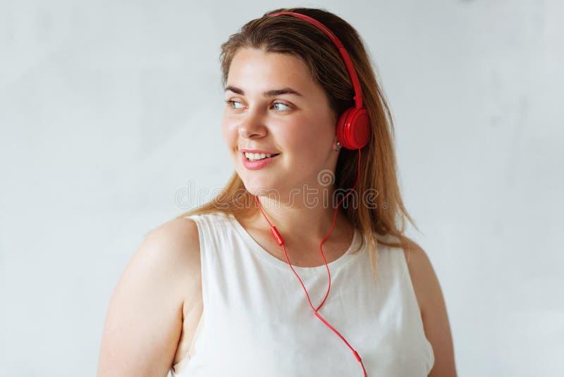 Młoda piękna kobieta jest ubranym czerwonych hełmofony obraz royalty free