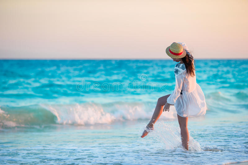 Młoda piękna kobieta na tropikalnej plaży w zmierzchu Tylny widok młoda dziewczyna w pięknym smokingowym tle morze zdjęcia royalty free