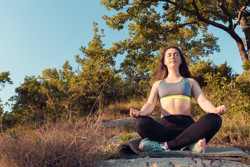 Młoda piękna kobieta ono uśmiecha się i medytuje w parku Zmierzchu ?wiat?o Pojęcie joga, sporty i medytacja, obrazy stock