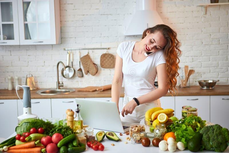 Młoda piękna kobieta opowiada na smartphone i używa notatnika w nowożytnej kuchni podczas gdy gotujący Zdrowy jedzenie i dieting obraz royalty free