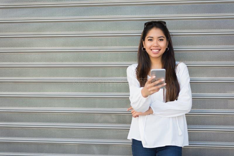 Młoda piękna kobieta opowiada wiadomość i texting z jej telefonem zdjęcie royalty free