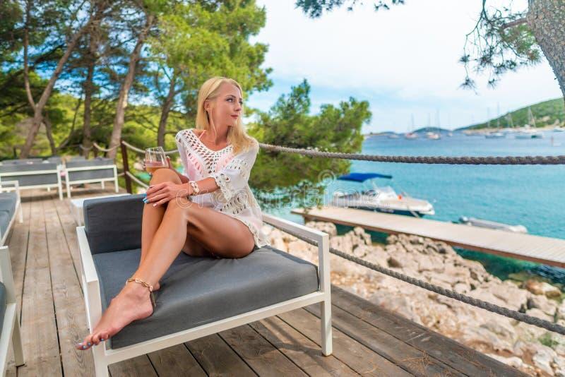 Młoda piękna kobieta pije białego wino relaksuje na otwartym tarasowym cieszy się widoku morze śródziemnomorskie w Chorwacja fotografia royalty free