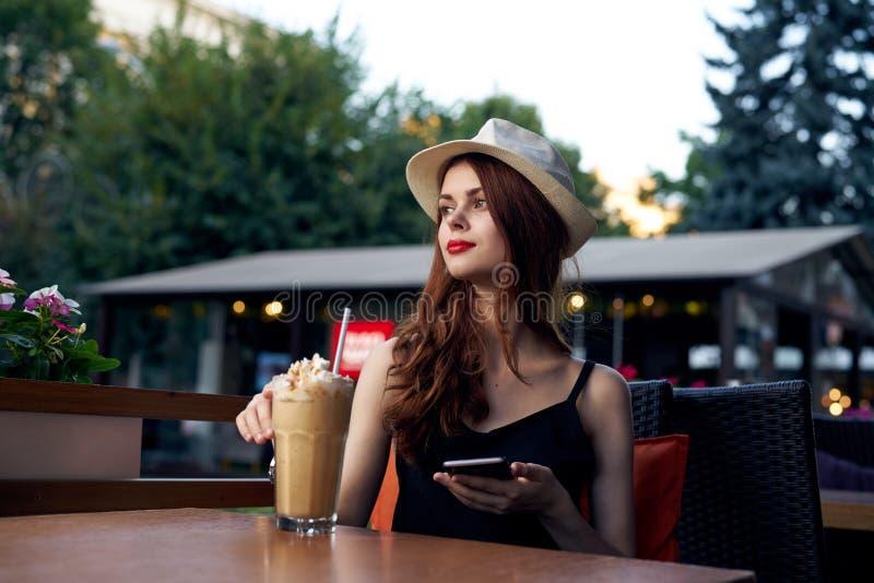 Młoda piękna kobieta pije kawę w kawiarni na ulicie w białym kapeluszu fotografia royalty free