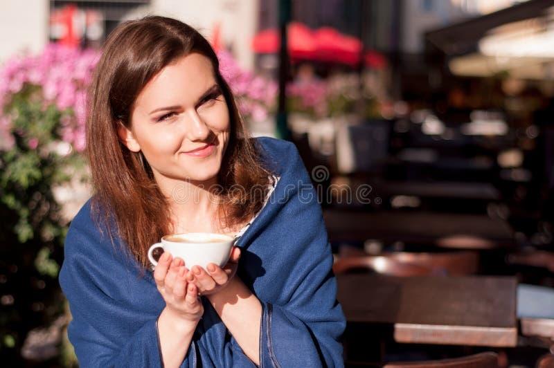 Młoda piękna kobieta pije ranek kawę w plenerowej kawiarni zdjęcia stock