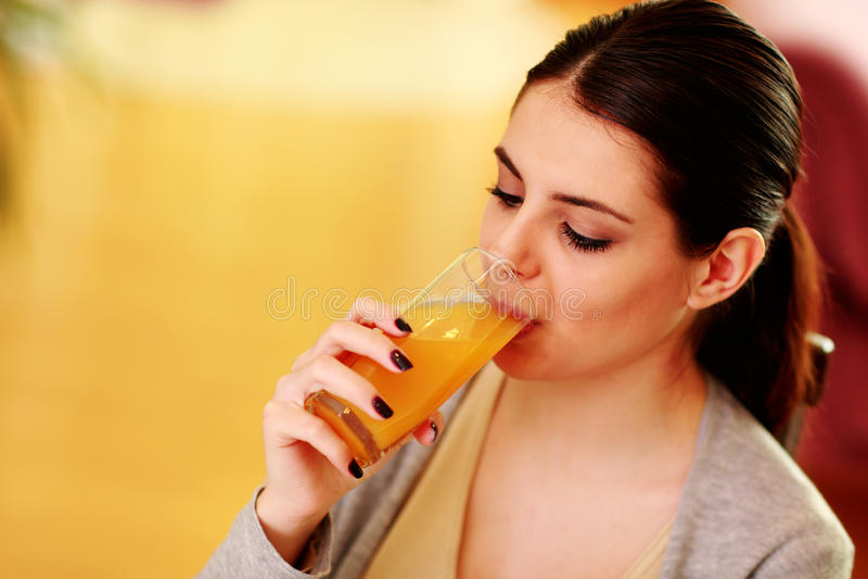 Młoda piękna kobieta pije sok pomarańczowego zdjęcia stock