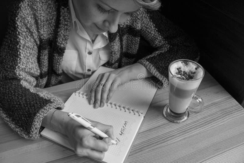 Młoda piękna kobieta pisze lista życzeń w otwartym notatniku w kawiarni Nowego Roku planowanie Sen i celu pojęcie obrazy royalty free