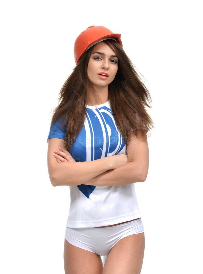 Młoda piękna kobieta pozuje patrzejący kamerę w pomarańczowym przeciwie zdjęcia royalty free