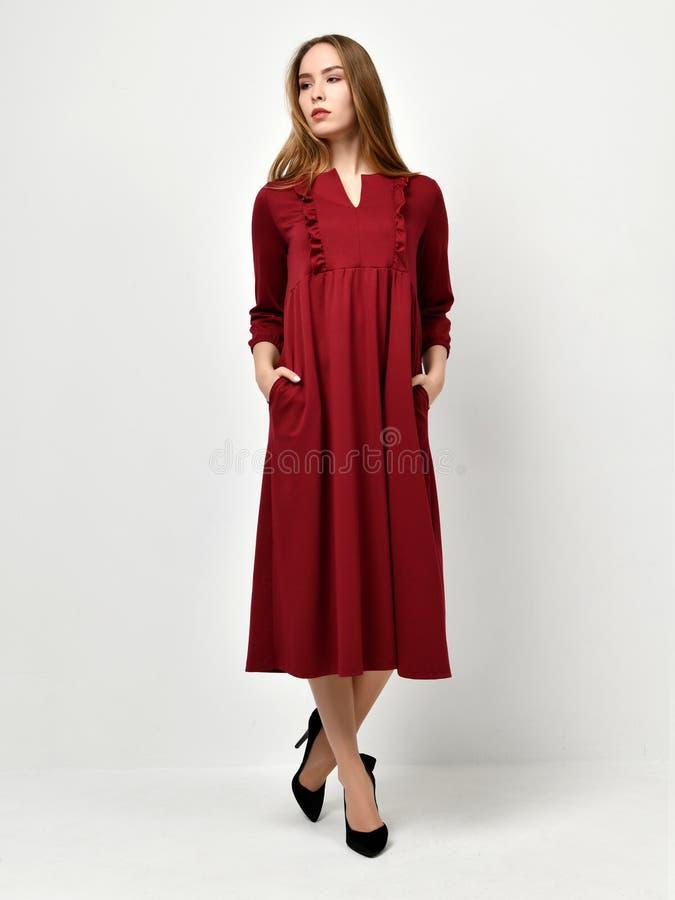 Młoda piękna kobieta pozuje w nowej mody czerwieni wzoru zimy sukni obraz stock