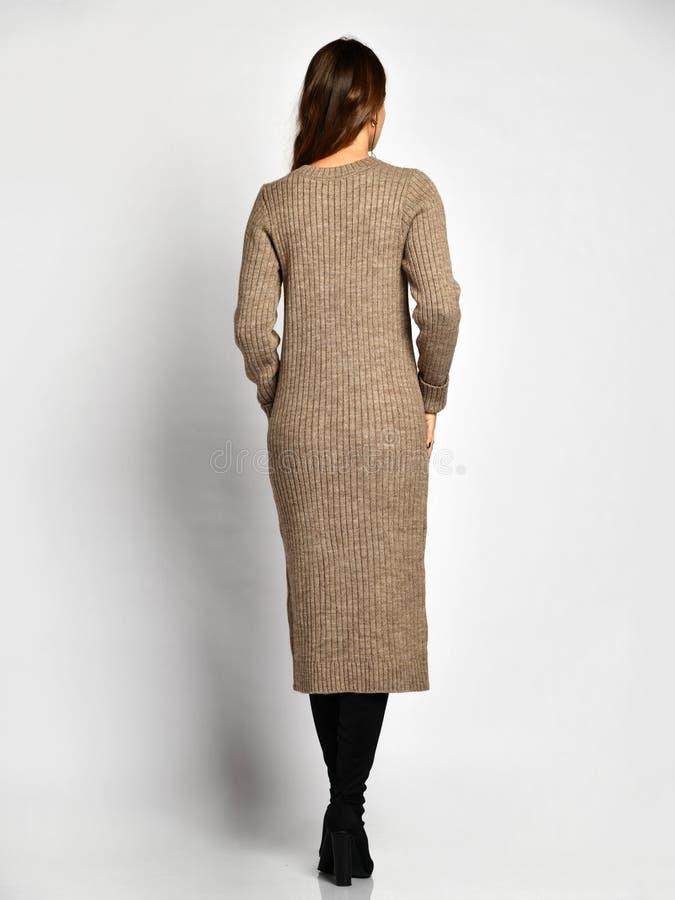 Młoda piękna kobieta pozuje w nowej szarości mody zimy sukni na wysokości inicjuje pełnego ciało zdjęcia stock