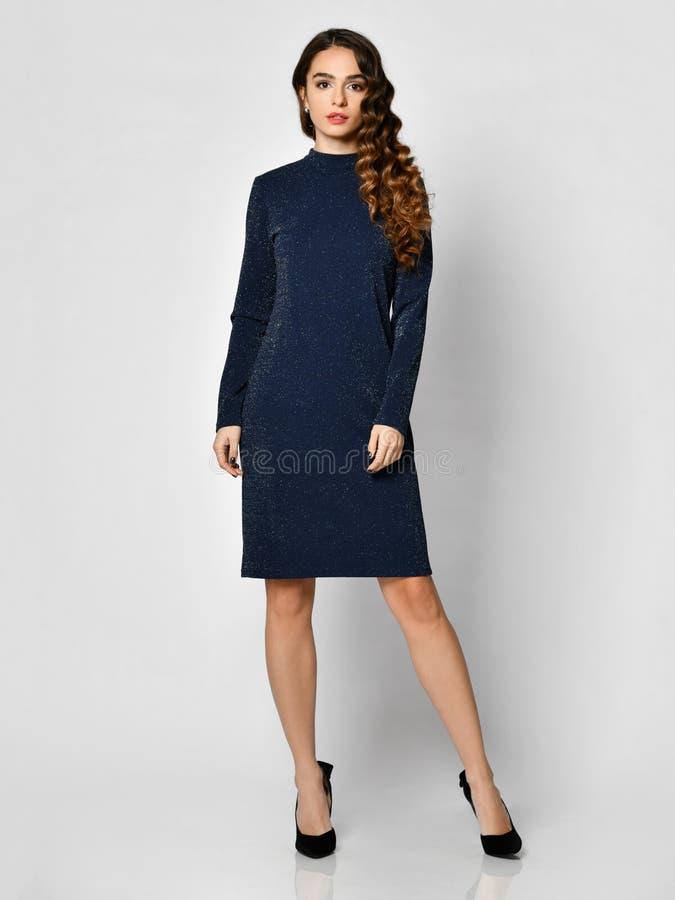 Młoda piękna kobieta pozuje w nowym zmroku - błękitna mody zimy suknia na bielu zdjęcia royalty free