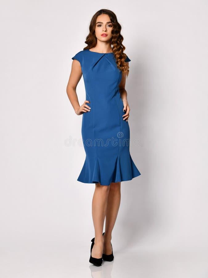 Młoda piękna kobieta pozuje w nowym zmroku - błękitna mody zimy suknia na bielu zdjęcie royalty free