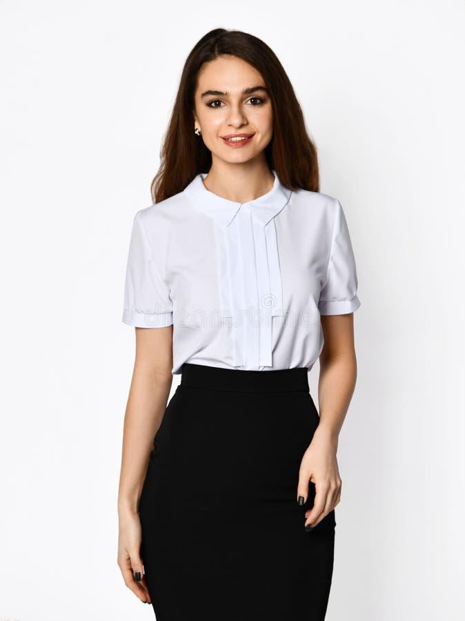 Młoda piękna kobieta pozuje w zmroku biurowym kostiumu Lekka bluzki i zmroku ołówka spódnica zdjęcia stock