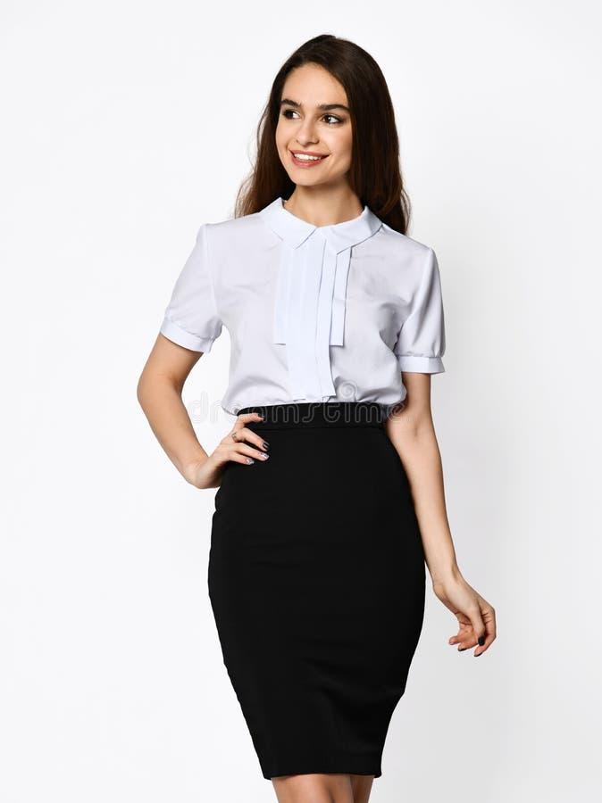 Młoda piękna kobieta pozuje w zmroku biurowym kostiumu Lekka bluzki i zmroku ołówka spódnica posiadanie odzież obraz royalty free