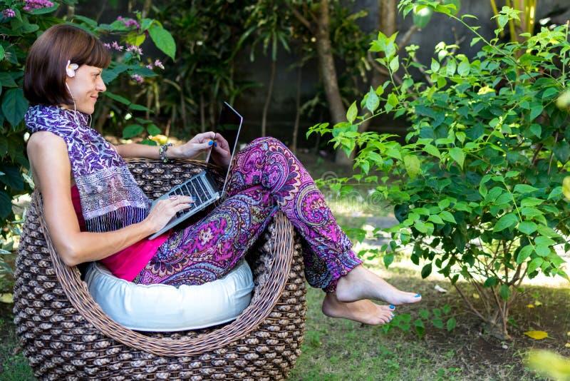 Młoda piękna kobieta pracuje z laptopem przy plenerowym tropikalnym parkiem, uśmiechem i szczęśliwym relaksującym uczuciem w rank obrazy royalty free