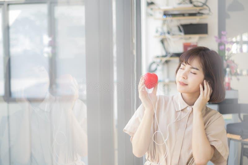 Młoda piękna kobieta słucha muzykę od jej serca obraz royalty free