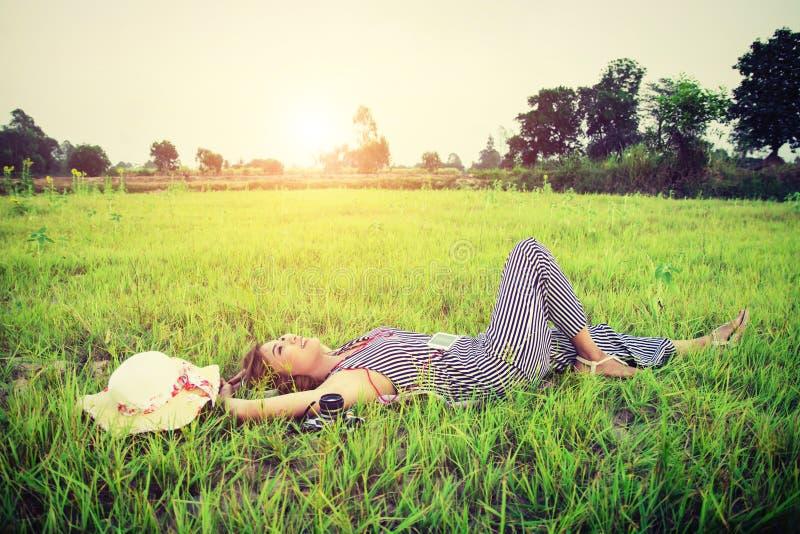 Młoda piękna kobieta słucha muzyka podczas gdy łgarski puszek na gre obraz stock