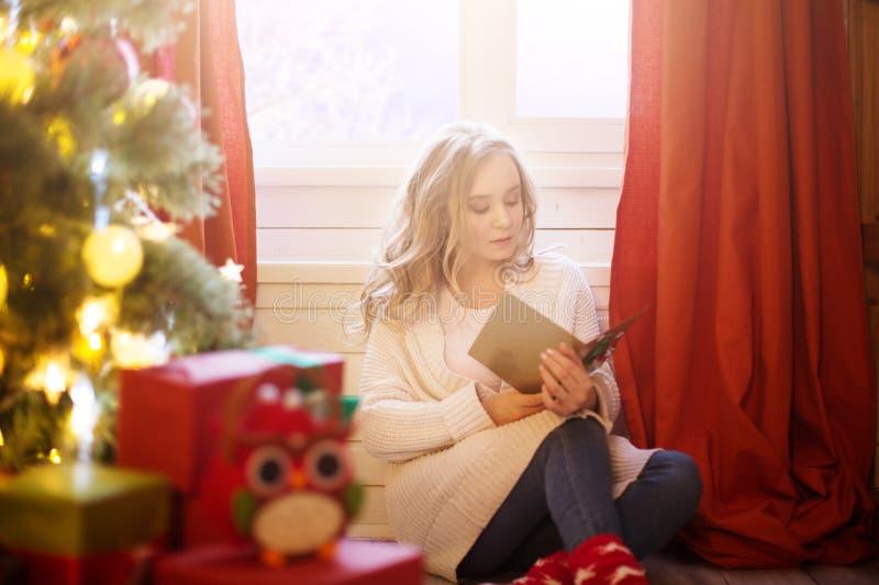 Młoda piękna kobieta siedzi blisko choinki i czytelniczych bożych narodzeń pocztówkowych obraz royalty free
