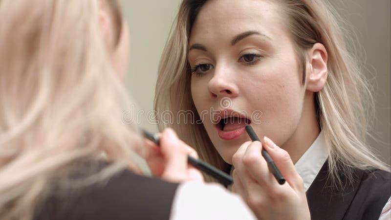 Młoda piękna kobieta stosuje czerwoną pomadkę na jej wargach obrazy stock