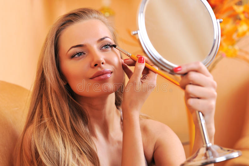 Młoda piękna kobieta stosuje makijaż obrazy royalty free