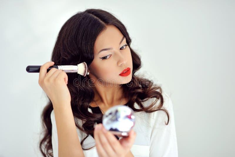 Młoda piękna kobieta stosuje ona uzupełniał, patrzejący w lustrze fotografia stock
