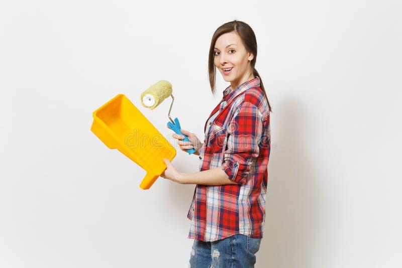 Młoda piękna kobieta trzyma farba rolownika dla ściennego obrazu i farby tacy odizolowywającej na bielu w przypadkowych ubraniach obrazy stock