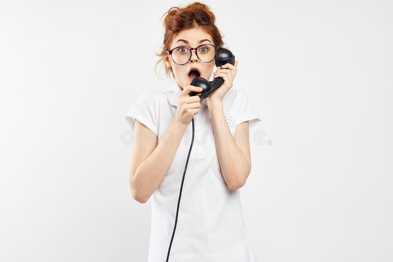 Młoda piękna kobieta trzyma stacjonarnego telefon na białym tle z szkłami, emocje obrazy stock