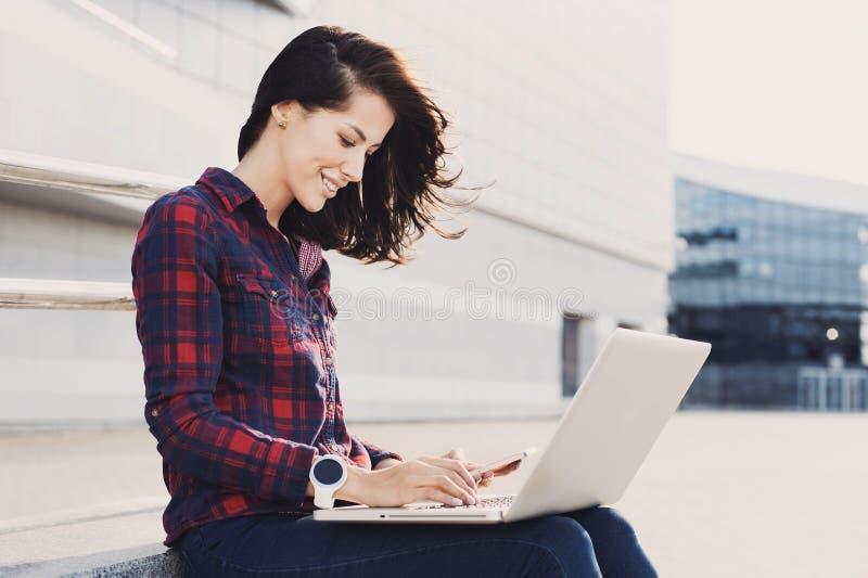 Młoda piękna kobieta używa laptop w miasto ulicie Pi?kna kobieta wr?cza dzia?anie na laptopie plenerowym obraz royalty free