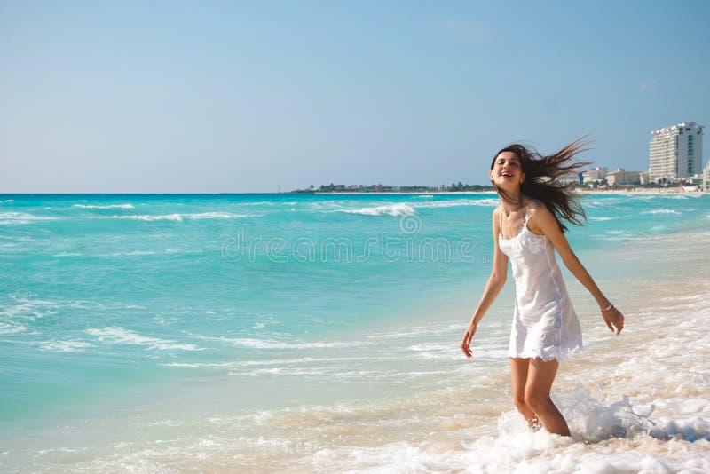 Młoda piękna kobieta w białej sukni jest zostająca o i śmiająca się obrazy royalty free